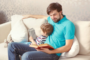 Young father reading on couch with young son.