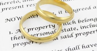 Wedding rings stacked upon a divorced agreement.